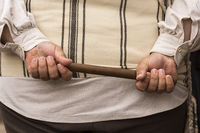 Man holding wooden baton in both hands behind his back