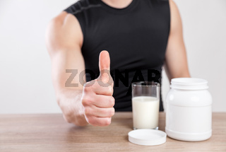 Closeup on a man with nutiotion and protein supplements on table