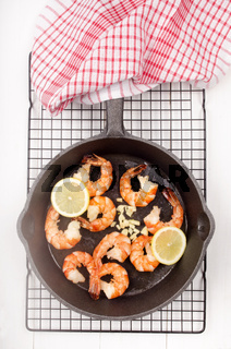 king prawns with lemon slice and garlic in a pan