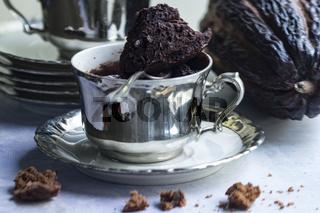 Tassenkuchen in versilberter antiker Tasse mit Kuchenkrümeln und einer Kakaofrucht