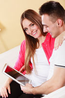 couple with tablet sitting on couch at home
