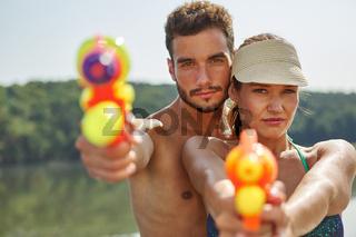Paar zielt mit Wasserpistolen im Sommer