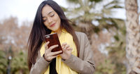 Happy young woman sending a text message