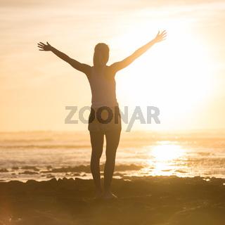 Free woman enjoying freedom on beach at sunset.