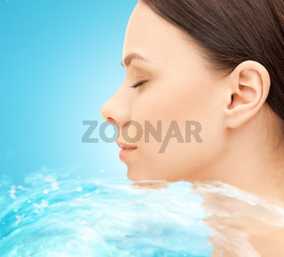 face of beautiful young woman and water splash