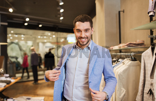 happy young man trying jacket on in clothing store