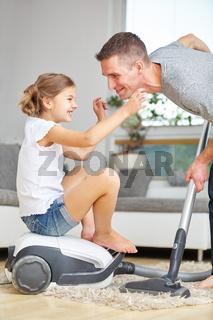 Vater und Mädchen mit Staubsauger lachen fröhlich