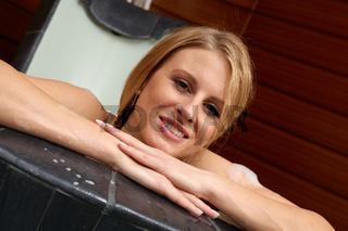 Junge Frau liegt in einem Spa in einer Badewanne
