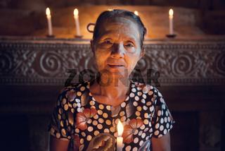 Burmese woman prayingwith candlelight