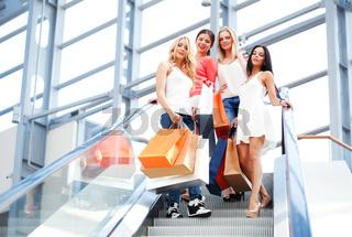 women standing on escalator