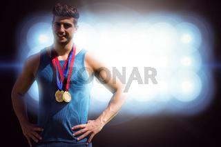 Composite image of portrait of athletic man holding medals