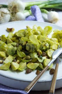 Rosenkohlsalat mit Cashewkernen und Rosinen auf einem weißen Teller mit Besteck