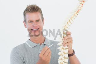 Smiling doctor showing anatomical spine