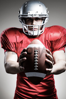 Composite image of portrait of determined american football player holding ball