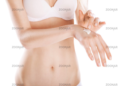 Woman applies cream on her hands isolated