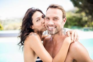 Woman kissing man near pool