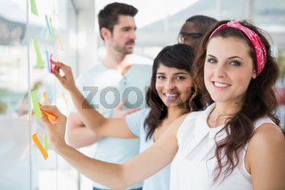 Smiling coworkers pointing sticky notes