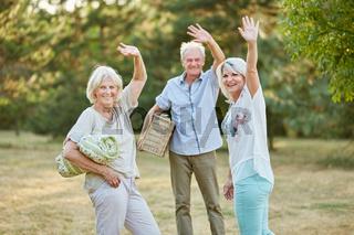 Senioren machen ein Picknick und winken