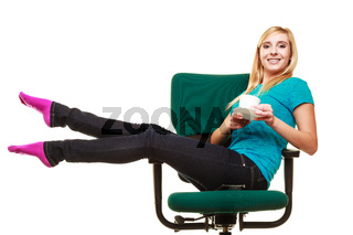 girl sitting on chair relaxing holds cup of tea or coffee.