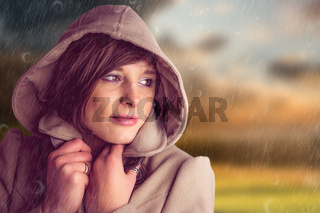 Composite image of beautiful woman wearing winter coat looking away