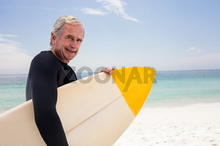 Portrait of senior man in wetsuit holding a surfboard