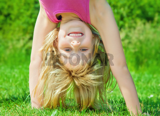child stands upside down