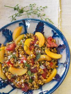 Bulgursalat mit Aprikosen und Tomaten in einer Keramik-Schale mit frischen Kräutern dekoriert