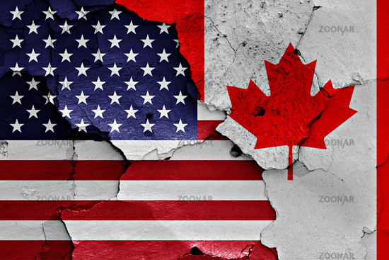 flags of USA and Canada painted on cracked wall