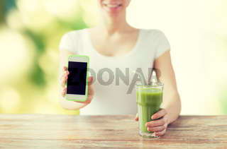 close up of woman with smartphone and green juice