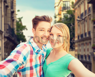 smiling couple with smartphone in city background