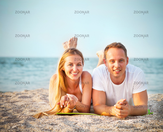 Laughing couple enjoying nature over sea background