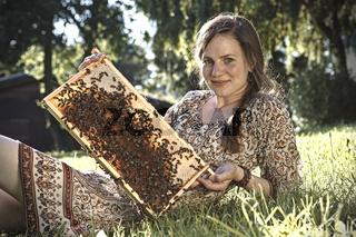 Imkerin mit Wabe voller Bienen
