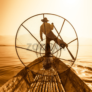 Burmese fisherman on bamboo boat catching fish in traditional way with handmade net. Inle lake