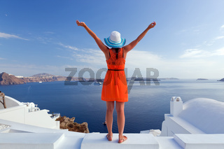 Happy woman in sun hat enjoying her holidays on Santorini island