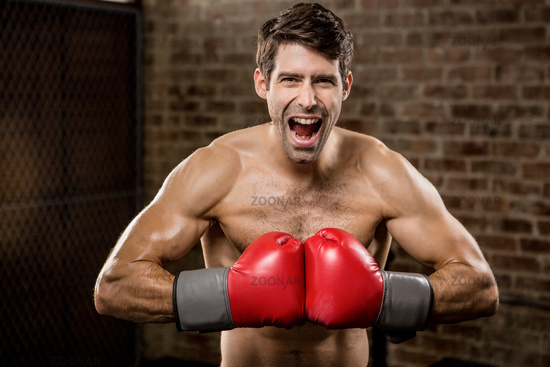 Shirtless man smiling while wearing boxing gloves
