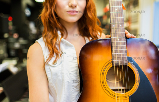 close up of woman with guitar at music store