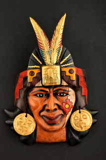 Indian Mayan Aztec ceramic mask with feather isolated on black