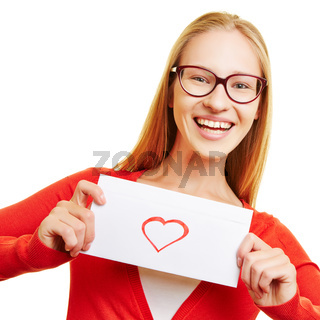 Mädchen zeigt Liebesbrief mit Herz