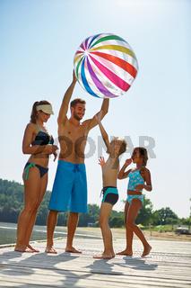 Familie mit Wasserball am See