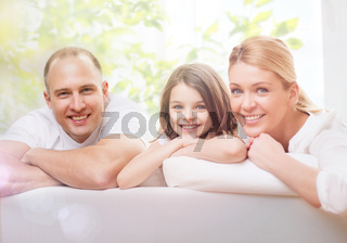 smiling parents and little girl at home