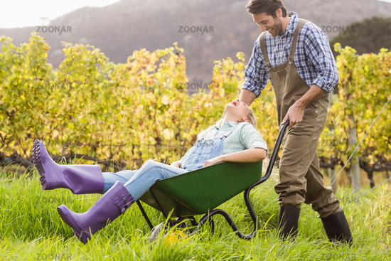 Laughing couple in dungarees pushing a wheelbarrow