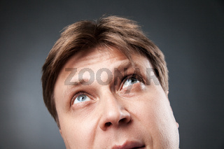 Curious adult man looking up