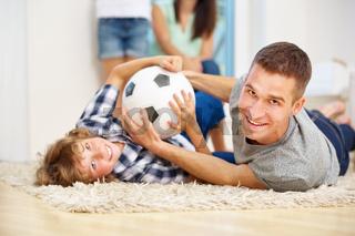 Vater und Junge toben mit Fußball im Wohnzimmer