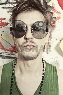Portrait of young punk in round sunglasses