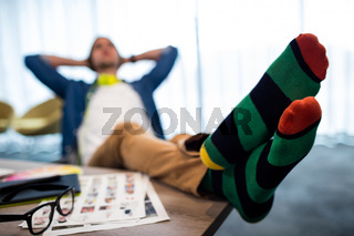 Casual man resting with feet on his desk