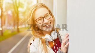 Lachende Frau mit Kopfhörer im Herbst