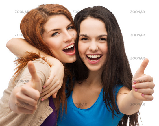 two smiling girls showing thumbs up