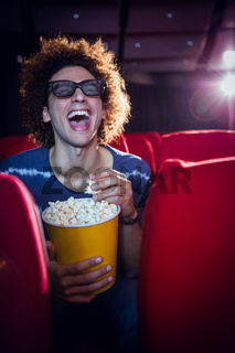 Young man watching a 3d film and eating popcorn