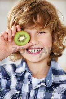 Junge hält Kiwi Hälfte vor ein Auge
