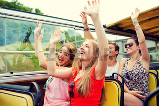 group of smiling friends traveling by tour bus
